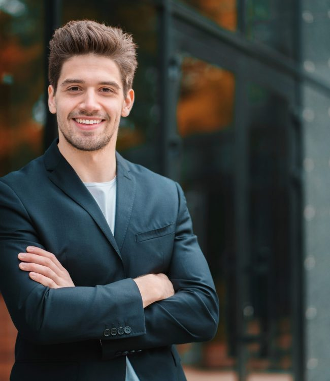 Portrait of young successful confident businessman in the city on office building background. Man in business suit looking to camera and smiling. Portraiture of handsome guy
